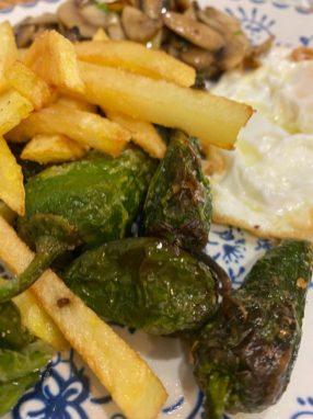 Huevos fritos con pimientos de Padrón, patatas fritas y champiñones al ajillo.