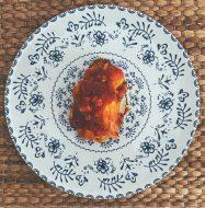 La merluza rebozada en su salsa de tomate