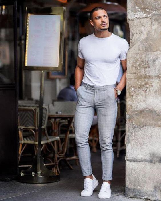 Calça de alfaiataria muito apertada marcando as partes baixas, masi camiseta e tênis brancos