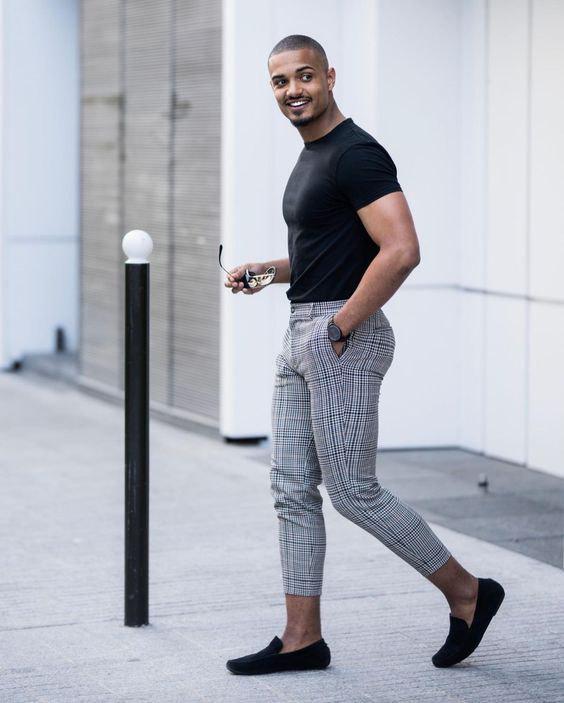 Calça cinza justíssima e de barra muito curta com camiseta básica preta e sapato slipper preto.