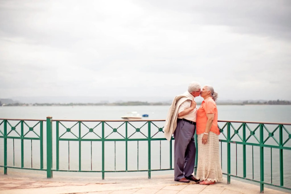 stylish elderly couple kissing on embankment