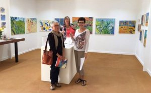 Pastels group photo showing 3 women and paintings in gallery