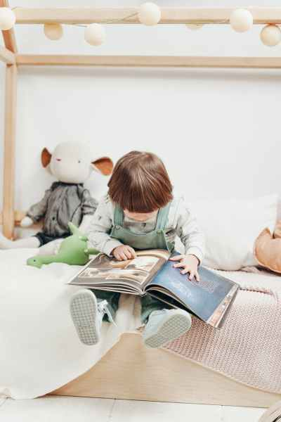 child in white long sleeve top and dungaree trousers sitting on bed reading book