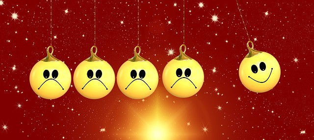Christmas ball balls all with unhappy faces apart from one with a smile