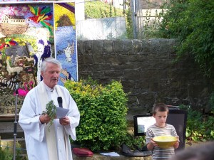 Vicar with rosemary, and helper with bowl of water.