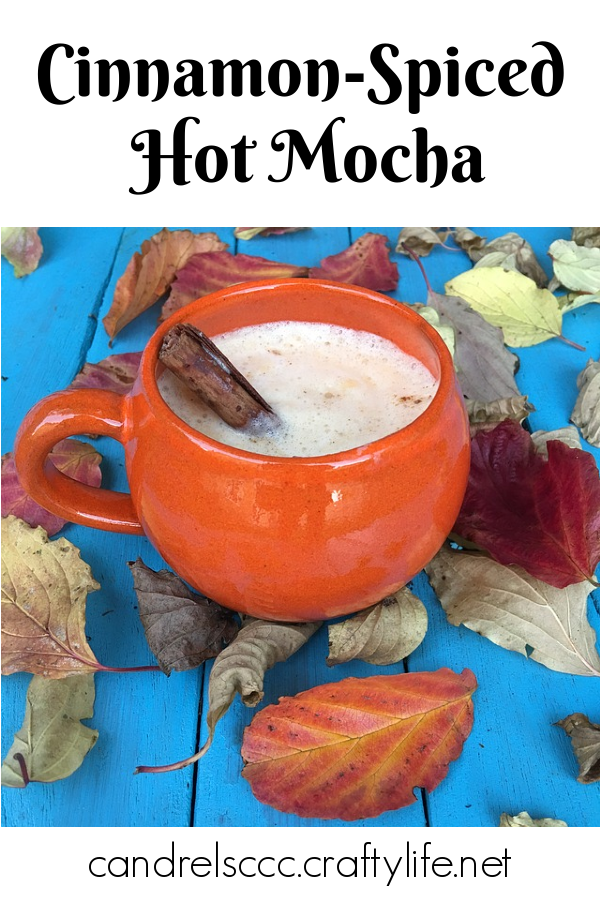 Cinnamon-spiced hot mocha in an orange mug with a cinnamon stick on a blue background with fall leaves