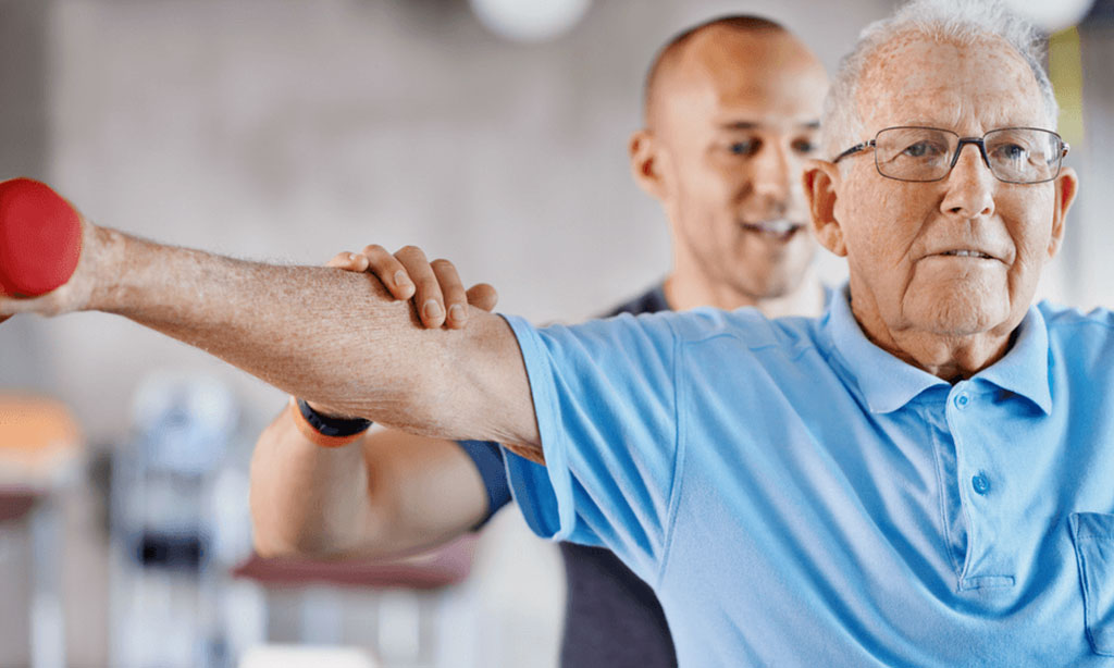 Personal trainer exercise helps senior man