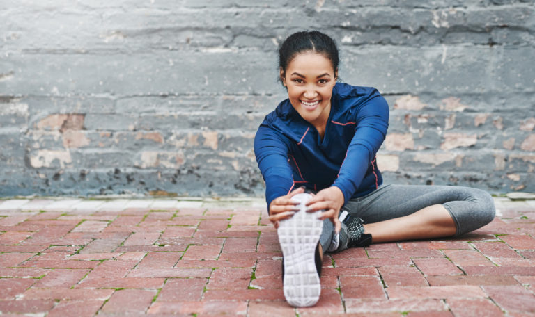 Shot of a sporty young woman stretching outside