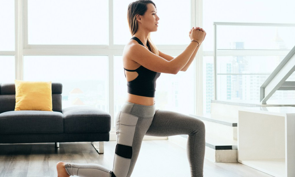 Attractive fit young woman in sports clothing working out while spending time at home