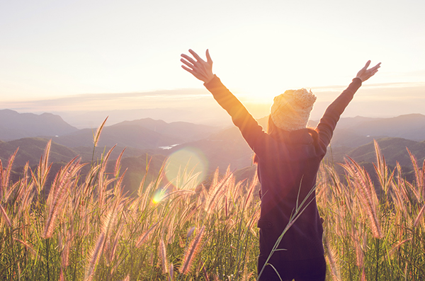 woman rise hand up on top of mountain and sunset sky