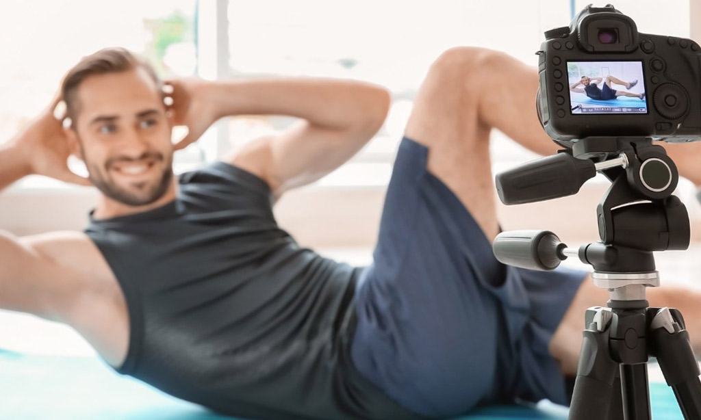 man making bicycle crunch on exercise mat and flexing abs at home