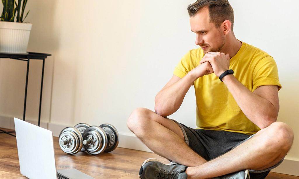 Man using laptop during workout at home