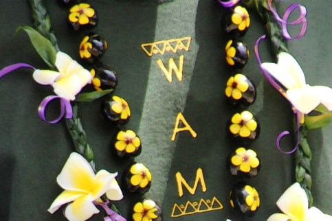 Beautiful leis frame the WAM logo.
