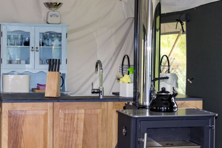 A view of the woodburning stove and kitchen area in Seren, one of our luxury glamping tents
