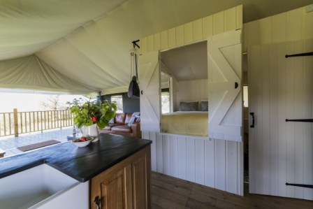 A view of the interior of the safari tent from the kitchen, showing the cabin bed