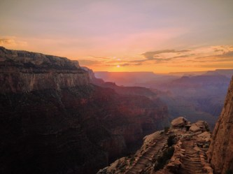 Photo of the Ooh-Aah switchback in the foreground and Grand Canyon sunset in the background