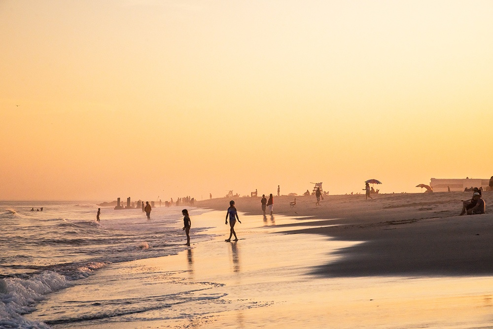 people in the ocean and walking on the beach during a summer sunset