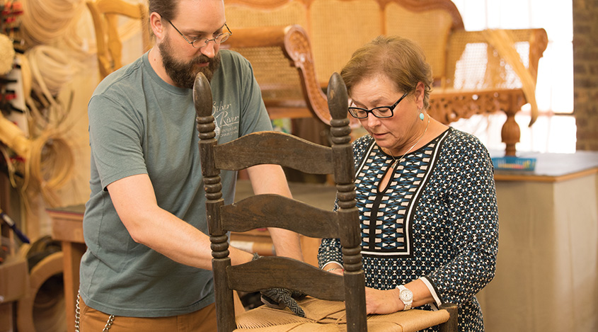 Dave Klingler, of Asheville's Silver River Center for Chair Caning, instructs a caning student.