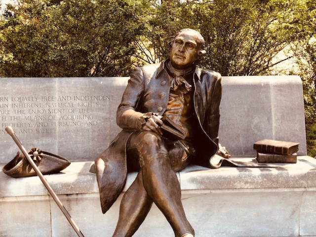 A statue of a person sitting on a bench Description automatically generated with low confidence