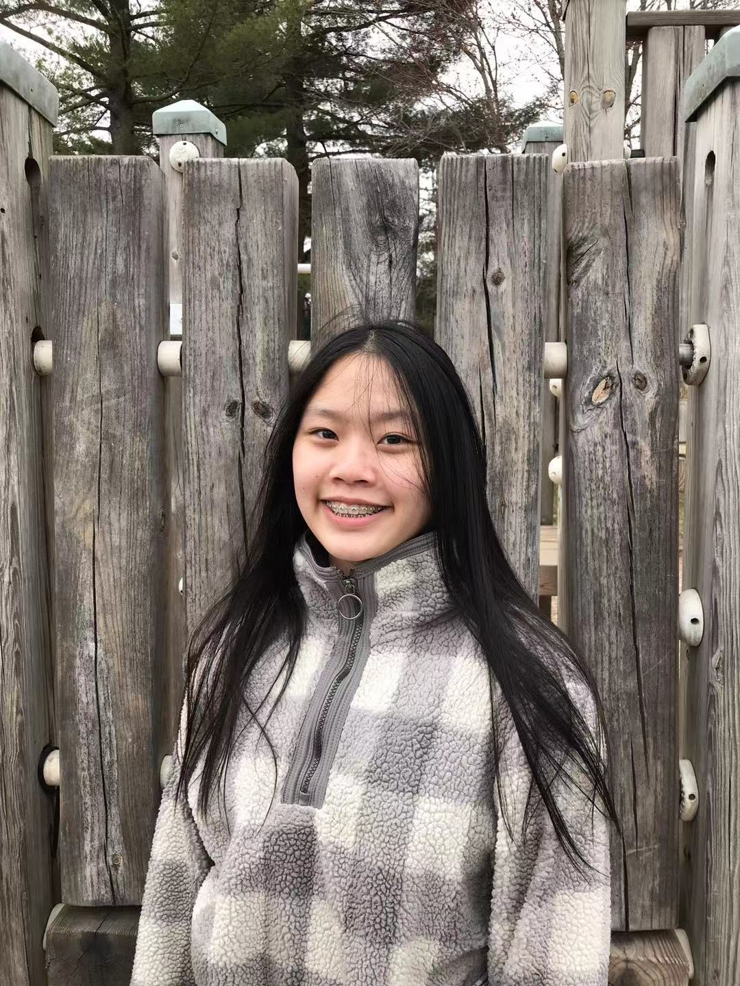 A person smiling in front of a wood fence  Description automatically generated with medium confidence
