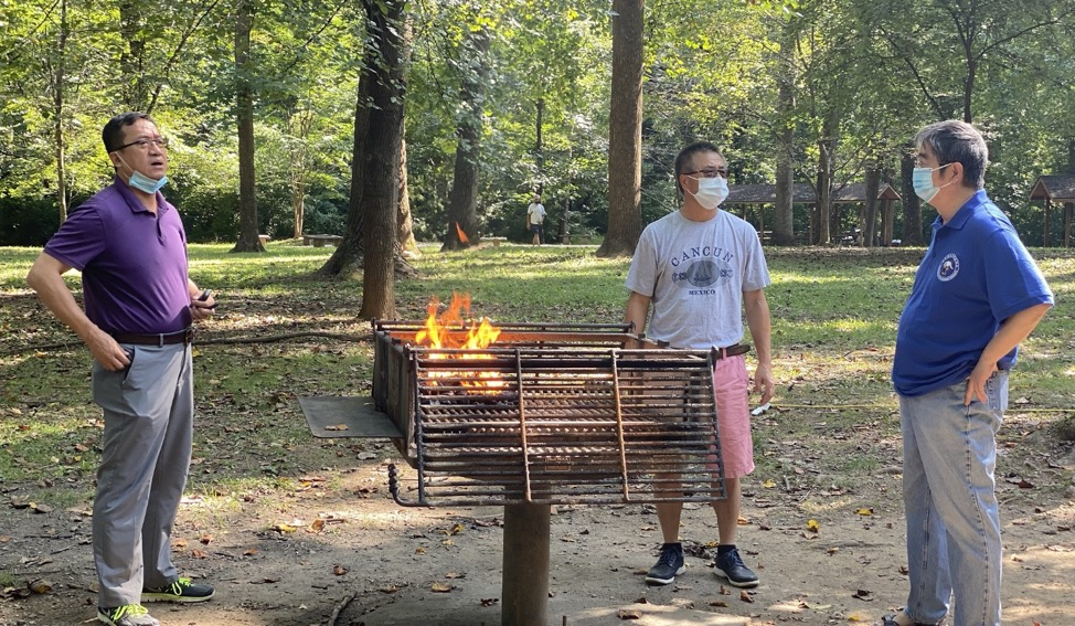 A group of people around a fire Description automatically generated with medium confidence