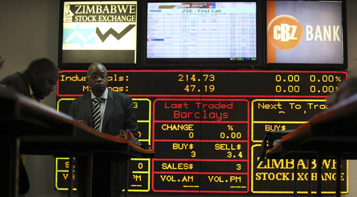 Stockbrokers work on the floor of the Zimbabwe Stock Exchange in Harare