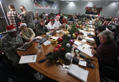 Volunteers take phone calls from children asking where Santa is and when he will deliver presents to their house, during the annual NORAD Tracks Santa Operation, at the North American Aerospace Defense Command, or NORAD, at Peterson Air Force Base, in Colorado Springs, Colo., Monday Dec. 24, 2012. Over a thousand volunteers at NORAD handle more than 100,000 thousand phone calls from children around the world every Christmas Eve, with NORAD continually projecting Santa's supposed progress delivering presents. (AP Photo/Brennan Linsley