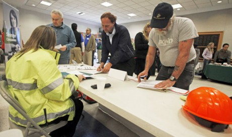 People fill out applications at the Green Mountain Flagging table at the annual Central Vermont Job Fair in Montpelier, Vt.   (AP Photo/Toby Talbot, File)