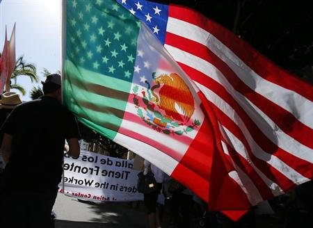 A youth carries national flags of the U.S. and Mexico through the streets of San Diego, during a May Day demonstration and march in California May. (REUTERS/Mike Blake)