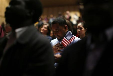 Immigrants stand for the invocation during a naturalization ceremony to become new U.S. citizens at Boston College in Chestnut Hill, Massachusetts. (REUTERS/Brian Snyder)