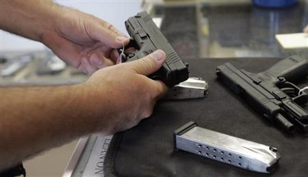 A customer inspects a 9mm handgun at Rink's Gun and Sport in the Chicago, suburb of Lockport, Illinois. (REUTERS/Frank Polich)
