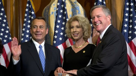 """Rep. Mark Meadows, R-N.C., right, participates in a mock swearing-in ceremony with Speaker of the House Rep. John Boehner in Washington. Emboldened conservatives who forced House Republican leaders to push a stopgap spending bill that unravels President Barack Obama's health care law are digging in for a long fight. """"Our resolve on this is unrelenting,"""" said Meadows, whose letter in July to Boehner and Majority Leader Eric Cantor, R-Va., called for collaboration to """"defund one of the largest grievances in our time"""" and attracted 79 Republicans. (AP Photo/ Evan Vucci)"""