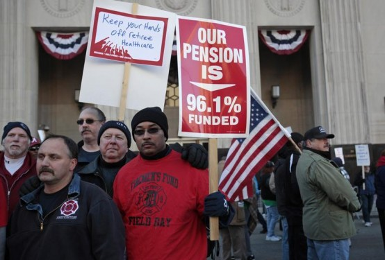 Detroit firefighter Darrell Tucker holds a sign in front of the Federal courthouse as he rallies against cuts in their city pensions and health care benefits during a protest against the city's municipal bankruptcy filing.    (REUTERS/Rebecca Cook)