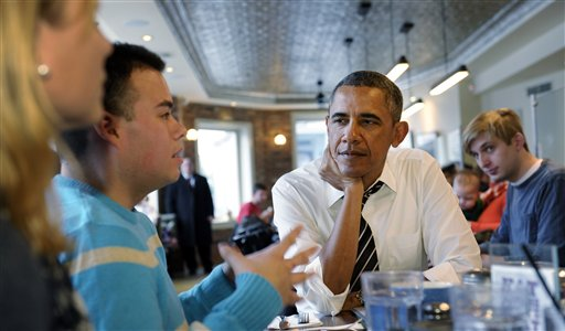 President Barack Obama listens to Andres Cruz, second from left, as he has lunch with five young people at The Coupe restaurant in the Columbia Heights section of Washington, Friday.  (AP Photo/Susan Walsh)