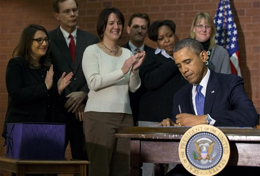 President Barack Obama signs the $1.1 trillion government spending bill.  (AP Photo/Jacquelyn Martin)