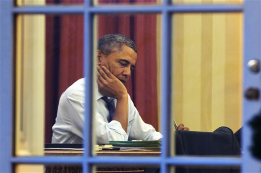 President Barack Obama works at his desk in the Oval Office of the White House in Washington, Monday, ahead of Tuesday night's State of the Union speech. (AP Photo/Jacquelyn Martin)