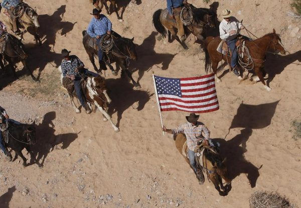 The Bundy family and their supporters fly the American flag as their cattle were released by the Bureau of Land Management back onto public land outside of Bunkerville, Nev. (AP Photo/Las Vegas Review-Journal, Jason Bean)