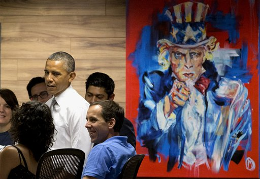 "President Barack Obama stands next to a painting of ""Uncle Sam,"" during a visit with workers at 1776, a hub for tech startups, Thursday in Washington.   (AP Photo/Jacquelyn Martin)"