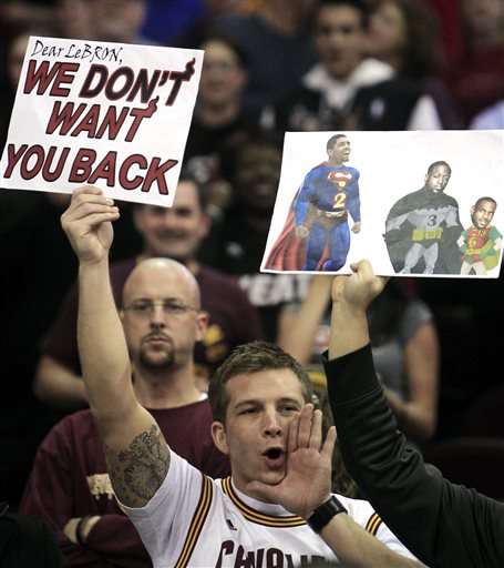 A Cleveland Cavaliers holds a sign and yells as Miami Heat's LeBron James is introduced  (AP Photo/Tony Dejak)