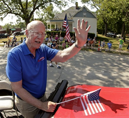 U.S. Sen. Pat Roberts waves to the crowd as he rides on the back of a pickup  (AP Photo/Charlie Riedel)