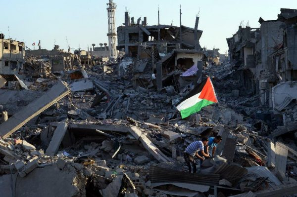 Residents walk through the rubble of their destroyed home as a Palestinian flag flutters in the wind (AFP Photo/Roberto Schmidt)