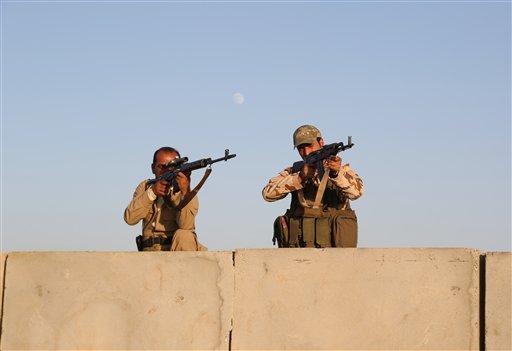 Kurdish Peshmerga fighters stand guard  (AP Photo/ Khalid Mohammed)