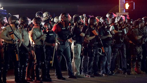 Police in riot gear mobilize during a standoff with protesters  (AP Photo/Charlie Riedel)