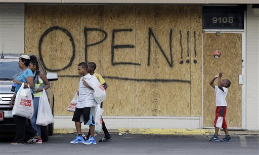 A young boy tosses a football as people walk past a business boarded up to protect against looting in Ferguson, Mo.  (AP Photo/Jeff Roberson)