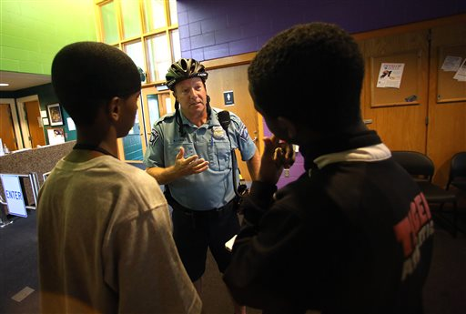 Minneapolis police officer Mike Kirchen talks with Mohamed Salat, left, and Abdi Ali at a community center where members of the Somali community gather in Minneapolis.  (AP Photo/The Star Tribune, Jim Gehrz, File)