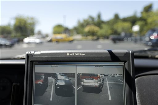 San Diego County Deputy Sheriff Ben Chassen reads the license plates of cars in a parking lot  (AP Photo/Gregory Bull)