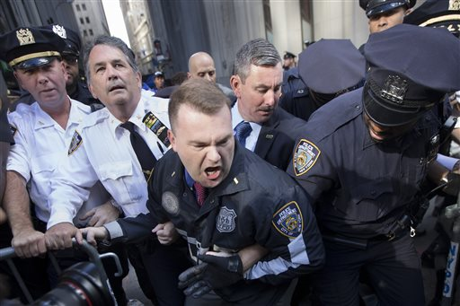 Police officers attempt to secure a barricade blocking protestors from Wall Street during a march demanding action on climate change and corporate greed  (AP Photo/John Minchillo)
