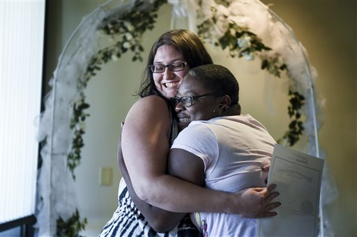 Jana Hayes, left, and Angie Hayes embrace under an altar at the Citizens Service Center in Colorado Springs, Colo. (AP Photo/The Colorado Springs Gazette, Michael Ciaglo)