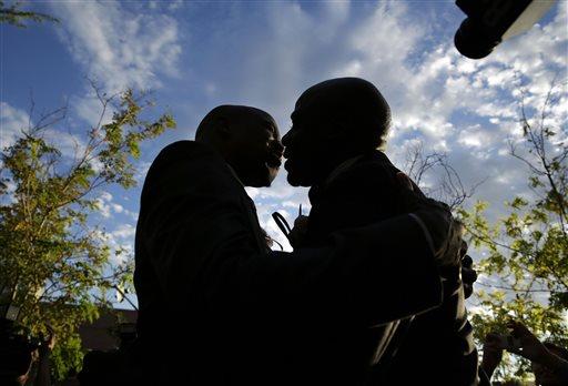 Sherwood Howard, left, embraces Nevada State Sen. Kelvin Atkinson as they get married outside of the Marriage License Bureau, Thursday in Las Vegas  (AP Photo/John Locher)