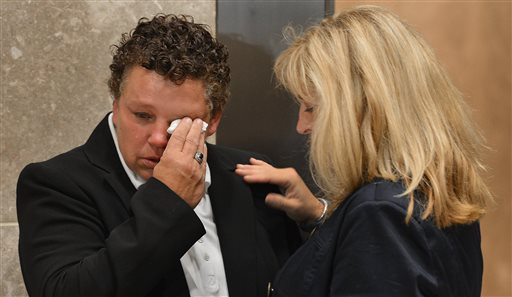 Vicki Britt wipes away tears as her partner, Trish Philbrook, comforts her during the announcement that there will be no marriages performed at the Wake County Courthouse in Raleigh, N.C. on Friday, (AP Photo/The News & Observer, Chuck Liddy)